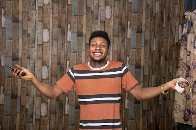 Jovem homem se sentindo animado enquanto segura seu smartphone e um papelzinho