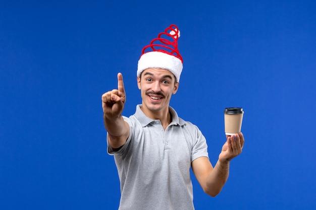 Jovem homem segurando a xícara de café na mesa azul com as emoções do feriado masculino de ano novo