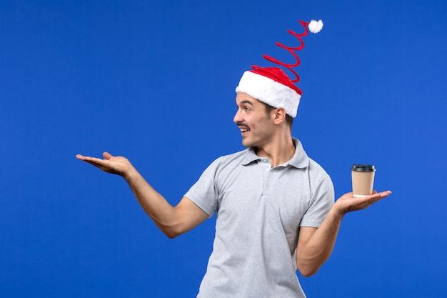 Jovem homem segurando a xícara de café na parede azul com emoções de ano novo masculino