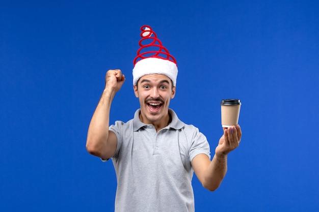 Jovem homem segurando a xícara de café na parede azul, emoção de feriado masculino de ano novo