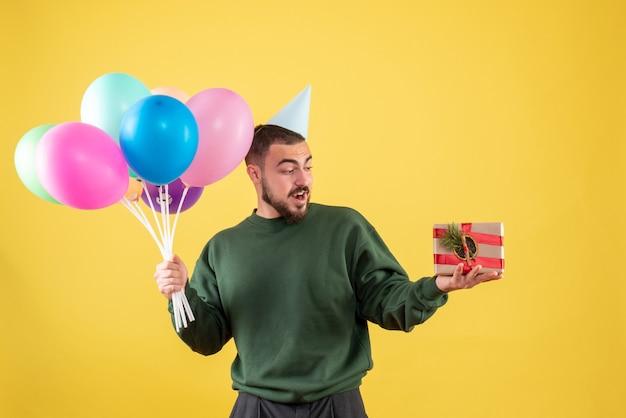 Jovem homem segurando balões coloridos e apresentar-se em um fundo amarelo de frente