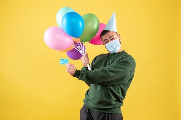 Jovem homem segurando balões coloridos e cartão do banco em fundo amarelo de frente