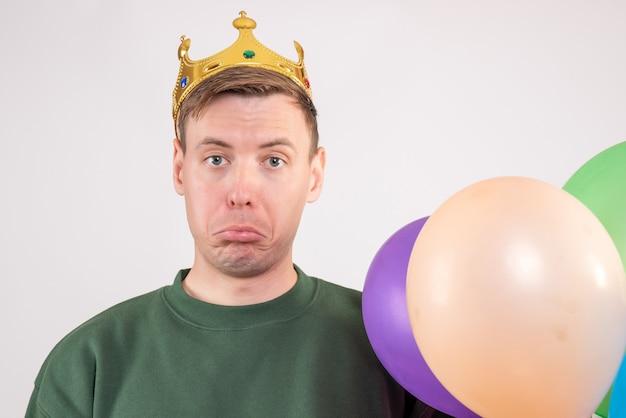 Jovem homem segurando balões coloridos em branco