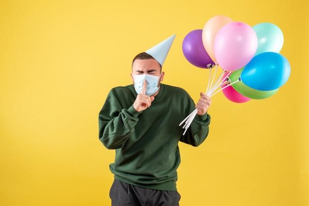 Jovem homem segurando balões coloridos em máscara estéril em fundo amarelo de frente