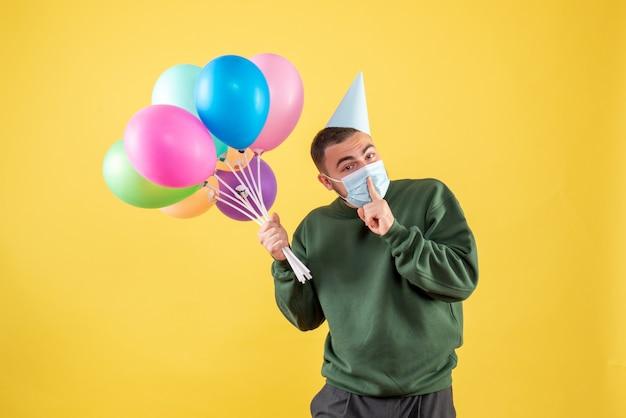 Jovem homem segurando balões coloridos na mesa amarela de frente