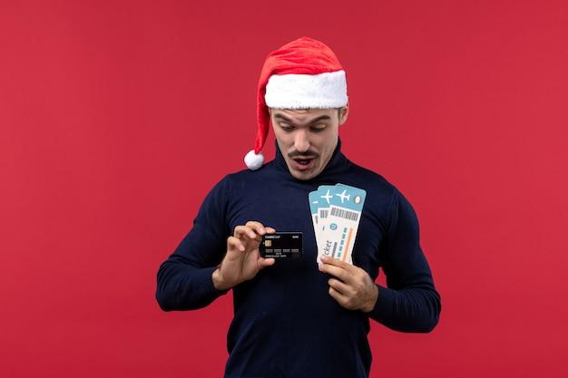 Jovem homem segurando o cartão do banco e os ingressos em fundo vermelho.