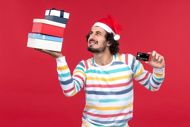 Jovem homem segurando o cartão do banco e presentes na parede vermelha dinheiro de ano novo de vista frontal