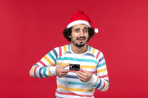 Jovem homem segurando o cartão do banco na parede vermelha clara de frente do sexo masculino vermelho emoção nas férias