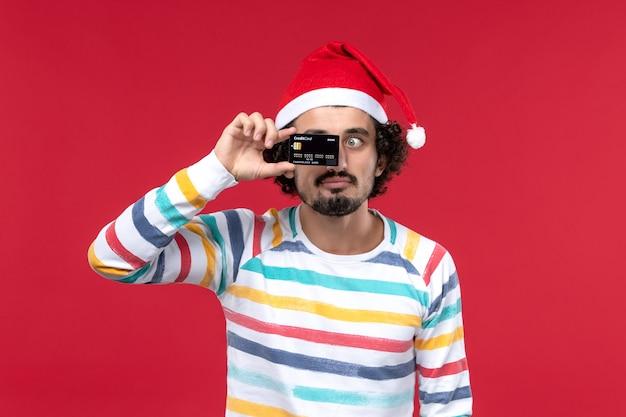Jovem homem segurando o cartão do banco na parede vermelha em emoção de feriado masculino vermelho