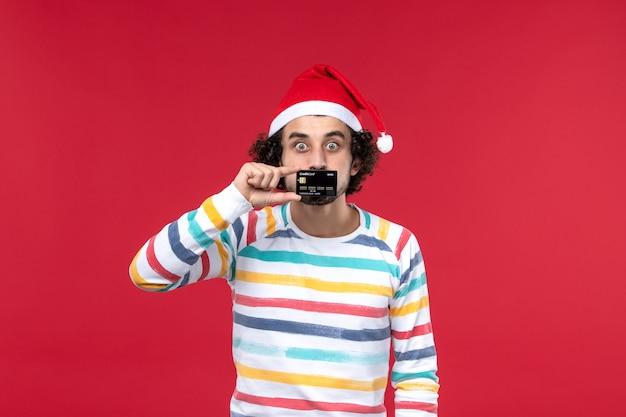 Jovem homem segurando o cartão do banco na parede vermelha na parede vermelha emoção masculina vermelha nas férias