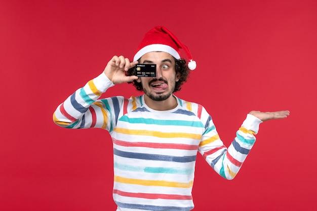 Jovem homem segurando o cartão do banco na parede vermelha vermelho masculino nas emoções do feriado de frente