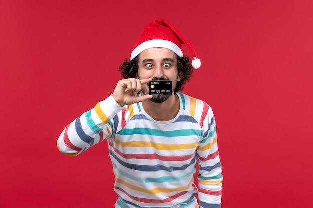 Jovem homem segurando o cartão do banco nas emoções da parede vermelha, vista frontal, feriado masculino vermelho