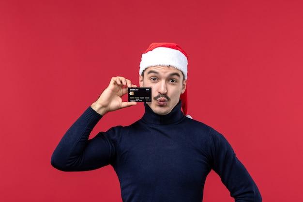 Jovem homem segurando o cartão do banco sobre fundo vermelho de frente