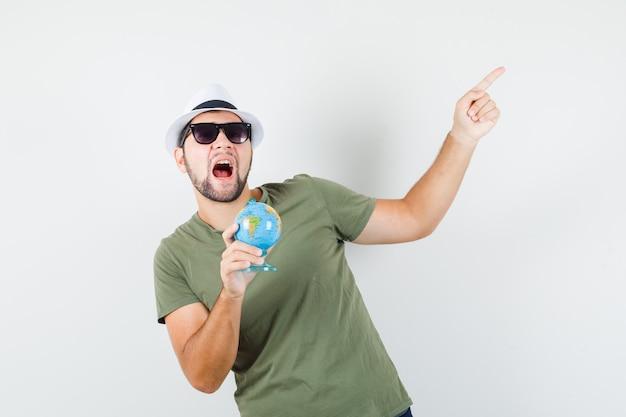 Jovem homem segurando o globo enquanto aponta para cima com camiseta e chapéu verdes