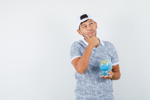 Jovem homem segurando o globo enquanto olha para cima com camiseta e boné e parece sonhador