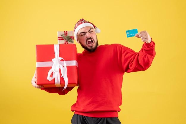 Jovem homem segurando o presente de natal e o cartão do banco em fundo amarelo de frente
