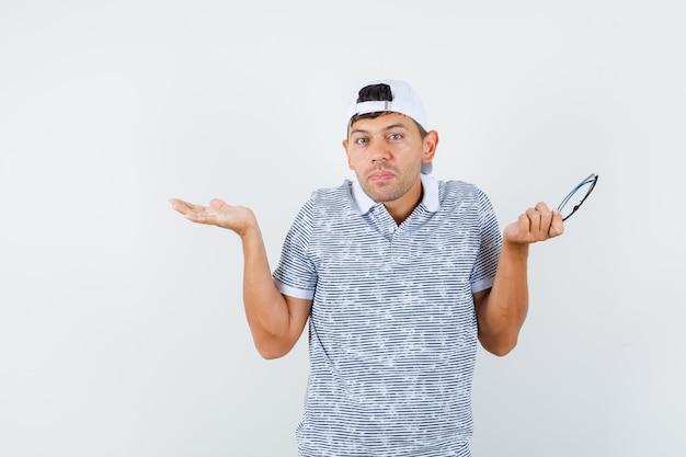 Jovem homem segurando óculos com um gesto de impotência na camiseta e boné e parecendo confuso