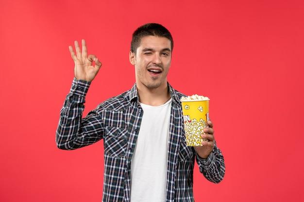 Jovem homem segurando pipoca e posando na parede vermelha filme de cinema