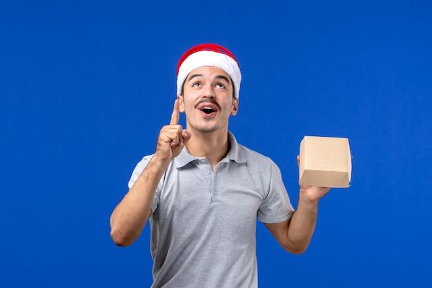 Jovem homem segurando um pacote de comida na parede azul de serviço masculino de comida de frente