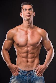 Jovem homem sem camisa muscular tem as mãos nos bolsos.