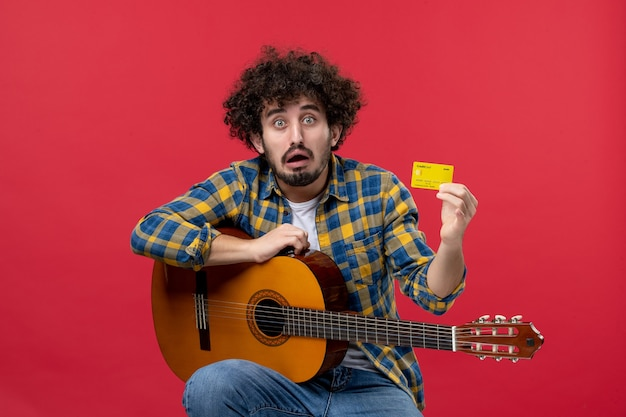 Jovem homem sentado com uma guitarra, segurando o cartão do banco na parede vermelha, vista frontal, aplausos, músico, tocar banda, concerto, música ao vivo
