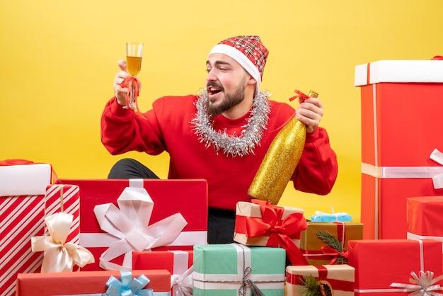 Jovem homem sentado de frente para um presente com champanhe em fundo amarelo