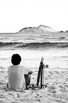 Jovem homem sentado em uma praia admirando o mar