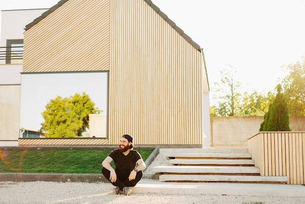 Jovem homem sentado na frente de sua nova casa, sorrindo e olhando para longe