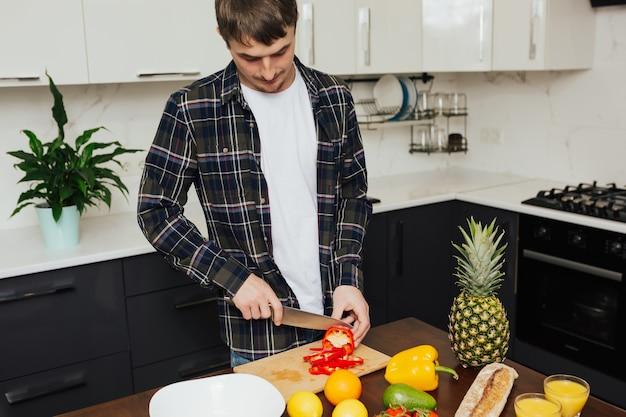 Jovem homem sério em pé perto da mesa, segurando uma faca e corta pimenta vermelha.