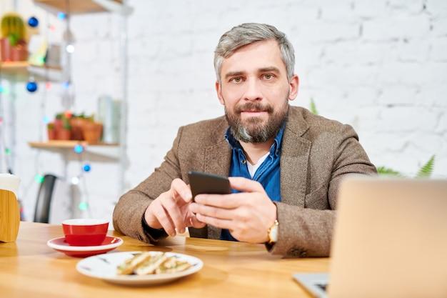 Jovem homem sério em trajes formais, sentado à mesa na frente da câmera, tomando chá com lanche e mensagens no smartphone