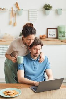 Jovem homem sério sentado à mesa e trabalhando em um laptop com a namorada em pé perto dele e o abraçando