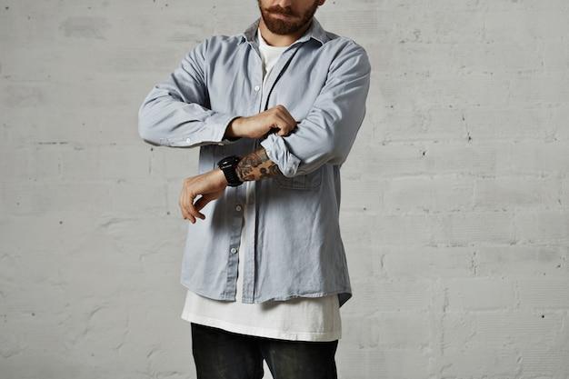 Jovem homem sério vestindo uma camiseta branca e uma camisa jeans azul claro arregaçando a manga direita mostrando um braço tatuado isolado no branco.