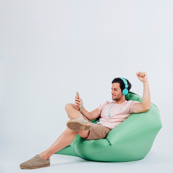 Jovem, homem, sofá, segurando, smartphone