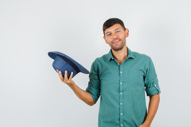 Jovem homem sorrindo e segurando um chapéu na camisa