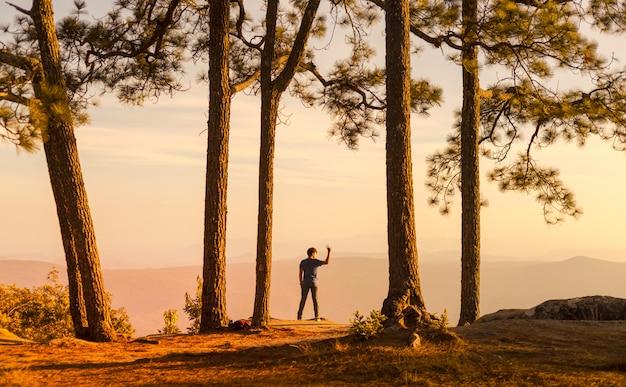 Jovem homem sozinho na floresta ao ar livre com a natureza do sol no fundo
