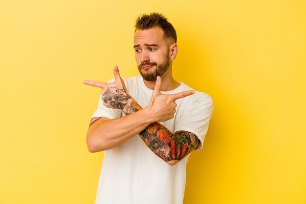Jovem homem tatuado caucasiano isolado em pontos de fundo amarelo para os lados, está tentando escolher entre duas opções.