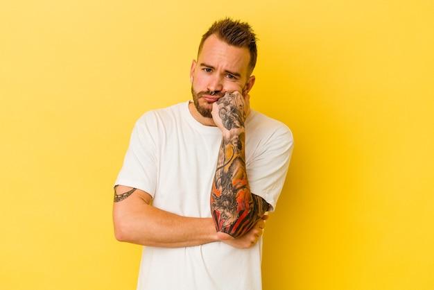 Jovem homem tatuado caucasiano isolado em um fundo amarelo, cansado de uma tarefa repetitiva.