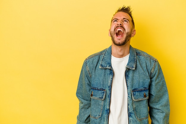 Jovem homem tatuado caucasiano isolado em um fundo amarelo, gritando com muita raiva, o conceito de raiva, frustrado.