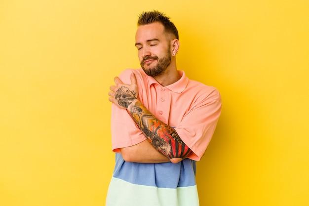 Jovem homem tatuado caucasiano isolado na parede amarela abraços, sorrindo despreocupado e feliz.