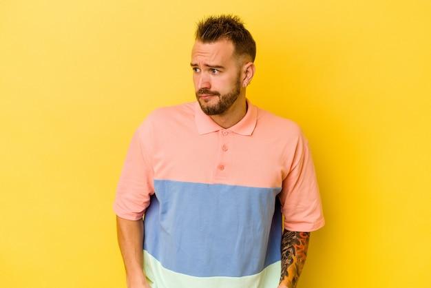 Jovem homem tatuado caucasiano isolado na parede amarela confuso, sente-se duvidoso e inseguro.