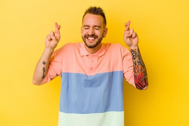 Jovem homem tatuado, caucasiano, isolado na parede amarela cruzando os dedos para ter sorte