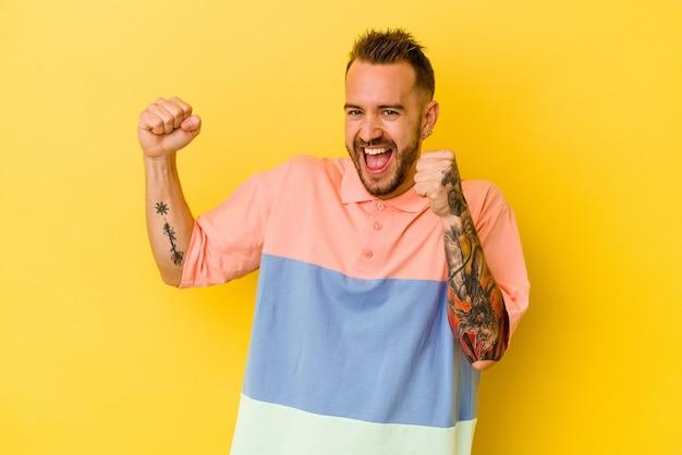 Jovem homem tatuado caucasiano isolado na parede amarela, dançando e se divertindo.