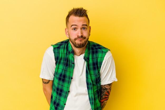 Jovem homem tatuado caucasiano isolado na parede amarela encolhe os ombros e abre os olhos confusos.