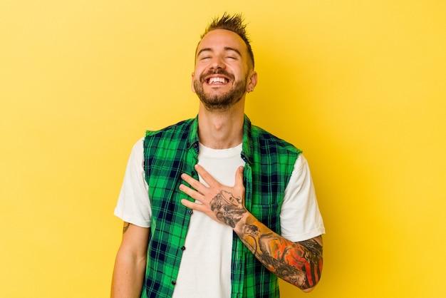 Jovem homem tatuado caucasiano isolado na parede amarela ri alto, mantendo a mão no peito.