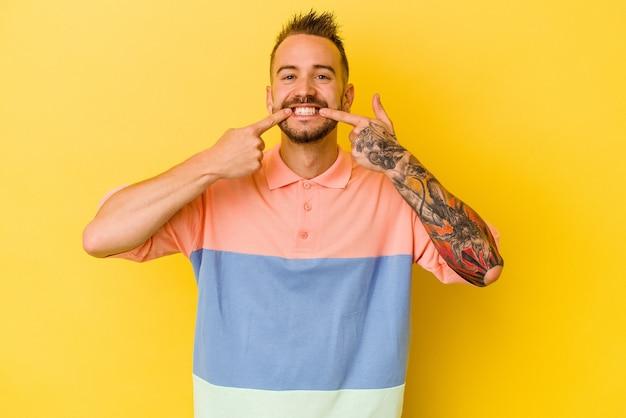 Jovem homem tatuado caucasiano isolado na parede amarela sorri, apontando o dedo para a boca.