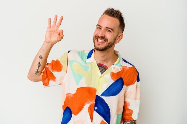Jovem homem tatuado caucasiano isolado na parede branca pisca um olho e segura um gesto de ok com a mão.