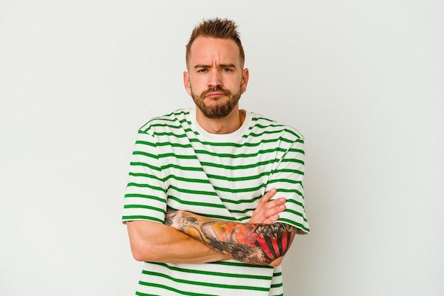 Jovem homem tatuado caucasiano isolado na parede branca sopra nas bochechas, tem uma expressão cansada. conceito de expressão facial.