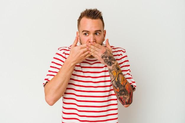 Jovem homem tatuado caucasiano isolado no fundo branco chocado cobrindo a boca com as mãos.