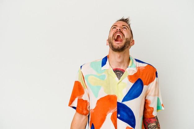 Jovem homem tatuado caucasiano isolado no fundo branco gritando com muita raiva, o conceito de raiva, frustrado.