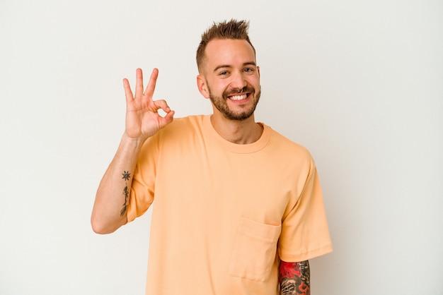 Jovem homem tatuado caucasiano isolado no fundo branco pisca um olho e segura um gesto de ok com a mão.